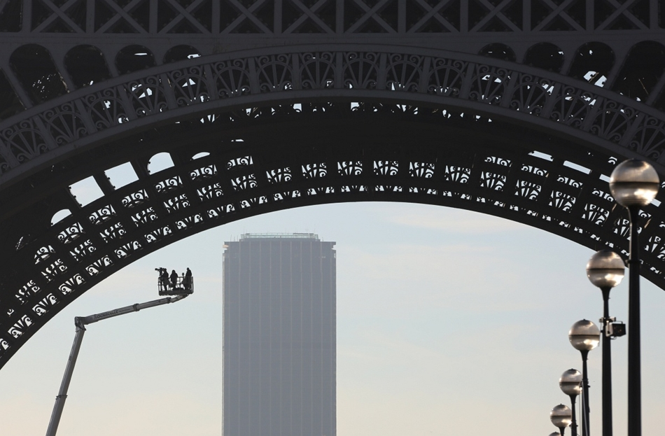 afp. hét képei - eiffel-torony, Párizs, napfelkelte, forgatás, 2015.09.02. This picture taken on September 2, 2015 at sunrise shows a media team taking footage from an elevated work platform, under the Eiffel Tower in Paris, with the Montparnasse Tower in